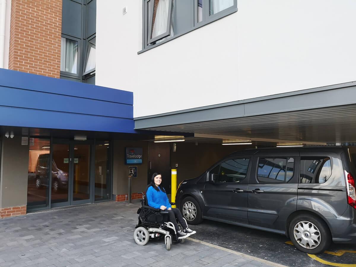 Emma sitting in her wheelchair beside her car in the Travelodge car park in a disabled parking bay.