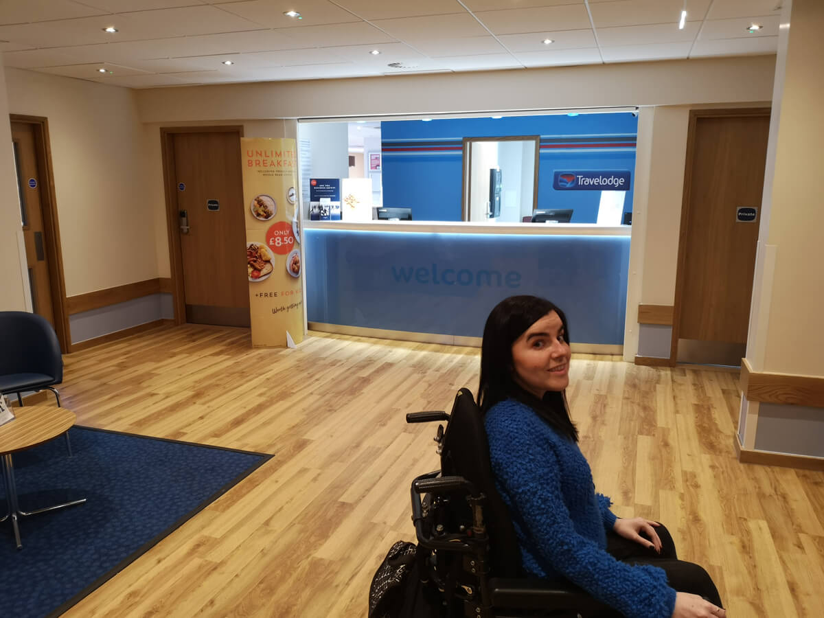Emma sitting in front of the reception desk at Travelodge Solihull. Emma is wearing a blue jumper and is turning her head to the camera and smiling.