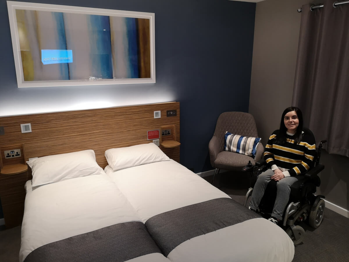 Emma sitting in her wheelchair in the wheelchair accessible SuperRoom at Travelodge.