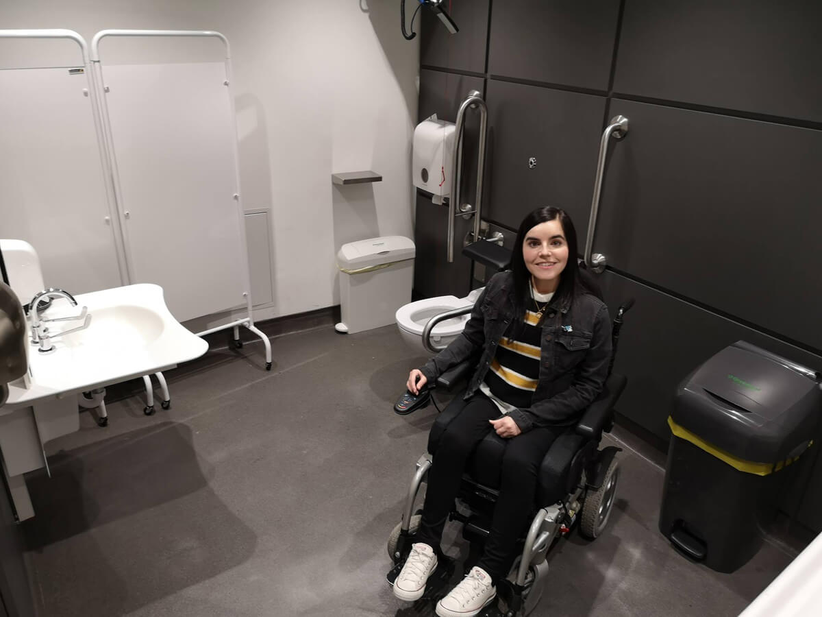 Emma sitting in her powered wheelchair in the Changing Places toilet at the SSE Hydro Glasgow.