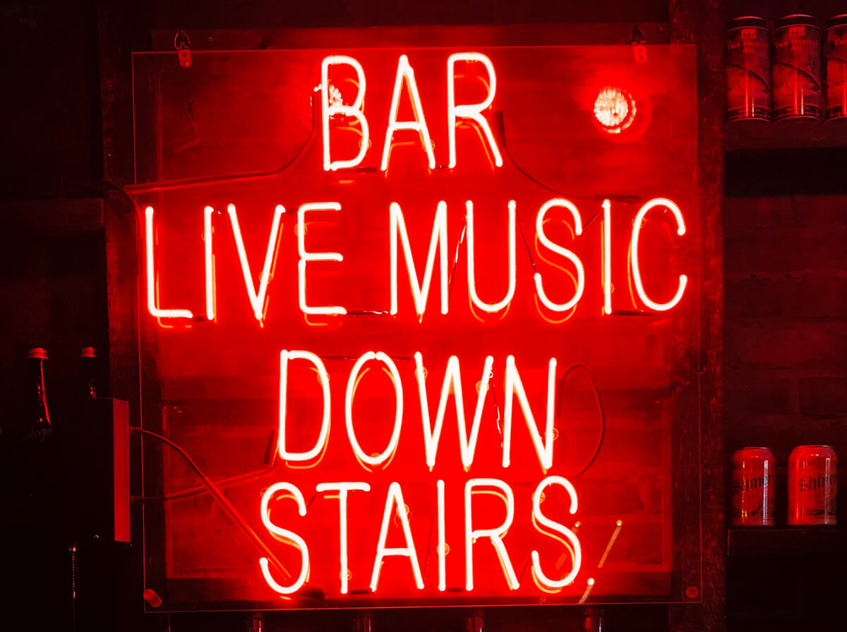 A red neon sign with the words 'BAR LIVE MUSIC DOWN STAIRS'
