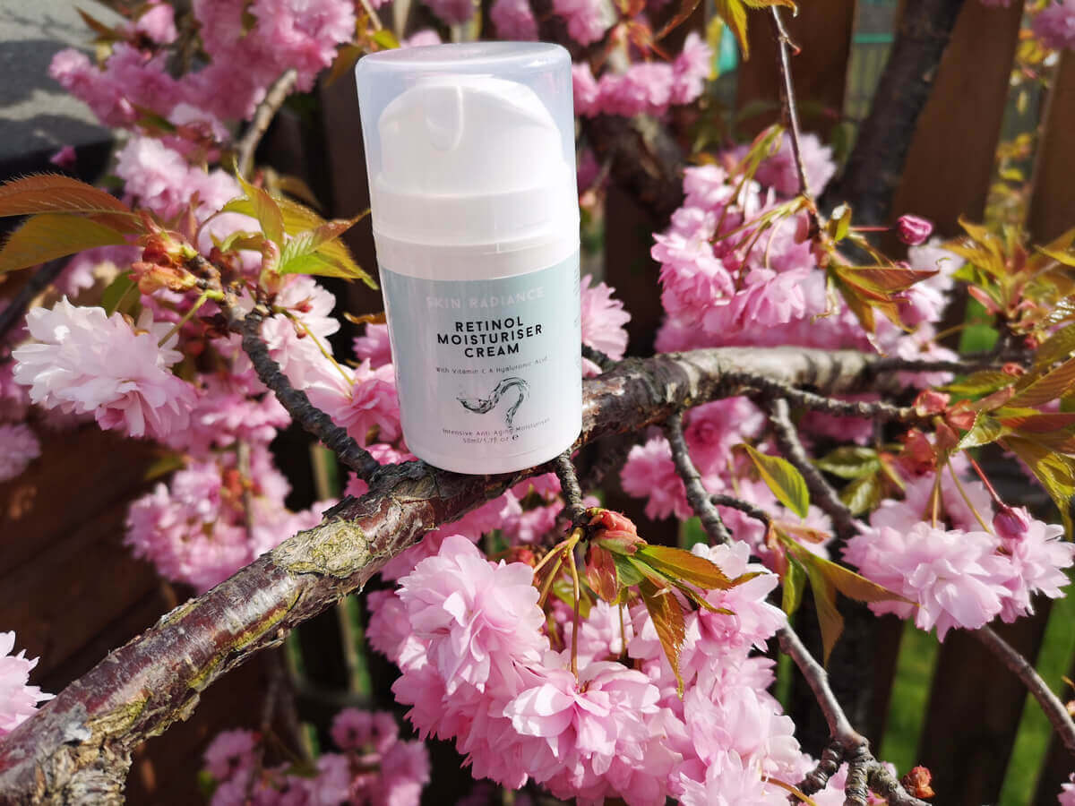 Skin Radiance Retinol Moisturiser Cream lying on a Cherry Blossom tree branch. The pink cherry blossom petals are in full bloom.