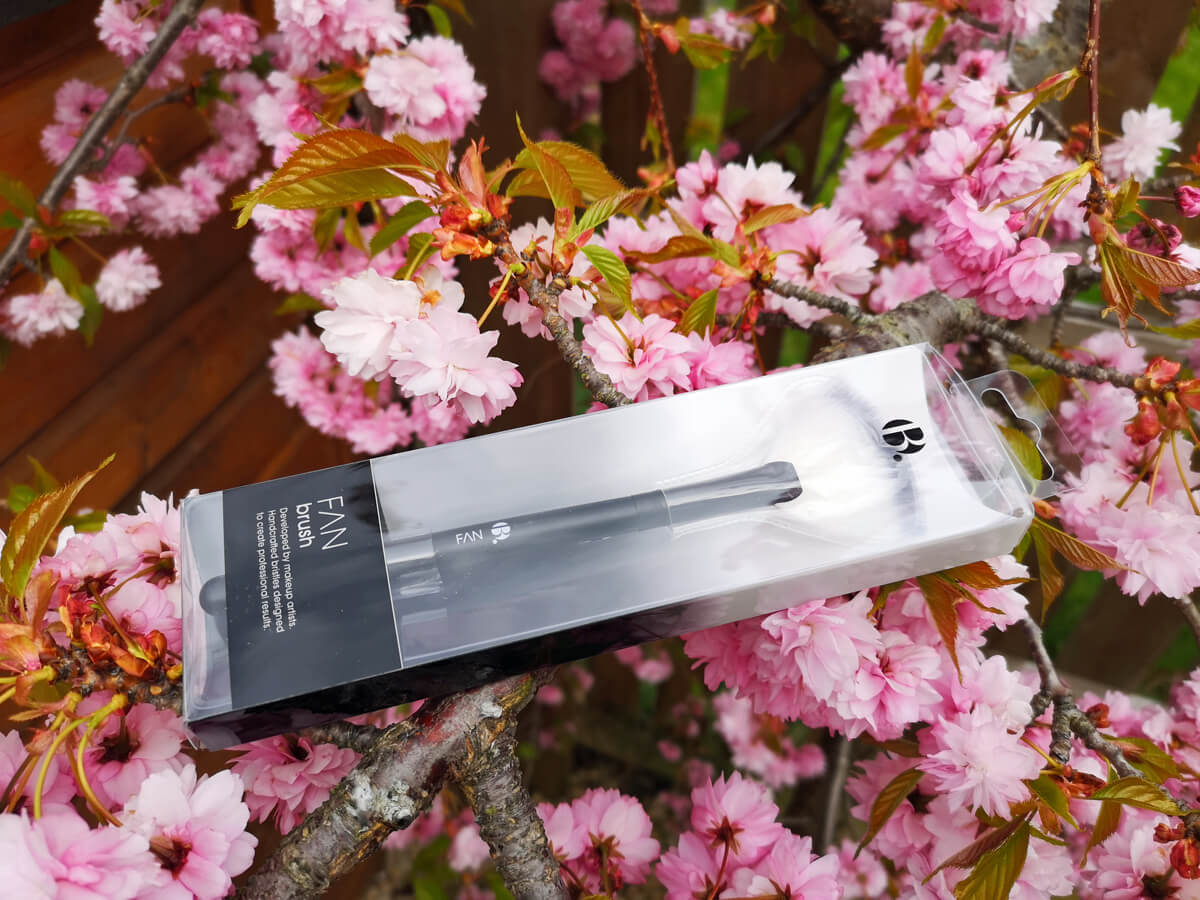 Official B. Fan Brush lying on a Cherry Blossom tree branch. The pink cherry blossom petals are in full bloom.