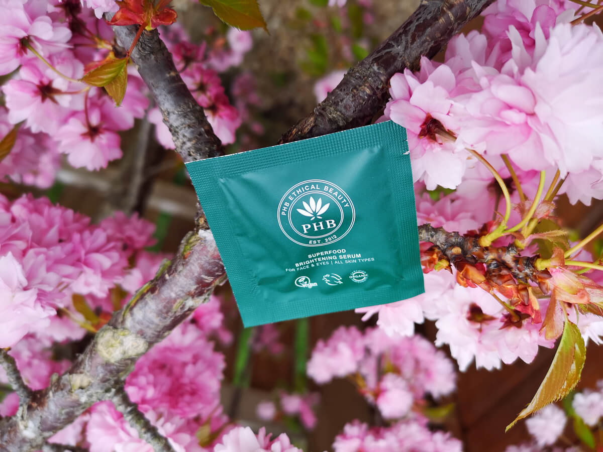 PHB Ethical Beauty Superfood Brightening Serum lying on a Cherry Blossom tree branch. The pink cherry blossom petals are in full bloom.