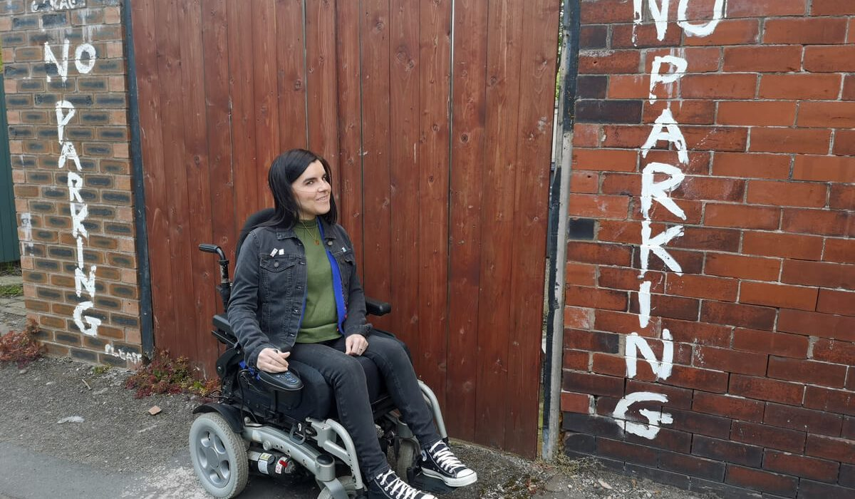 Emma is sitting in her wheelchair next to wooden gate and wall. The wall has the words 'No Parking' sprayed on them. Emma is looking mischievous because she is sitting in her wheelchair at a no parking sign.