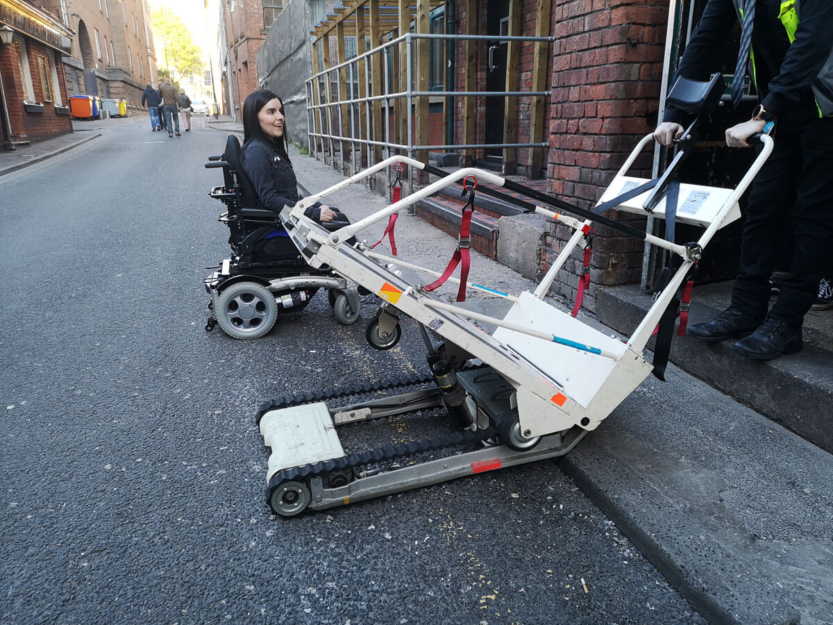 Emma sitting in her powered wheelchair outside the Albert Hall beside the stairclimber. She is waiting to drove onto the stairclimber and enter the venue.