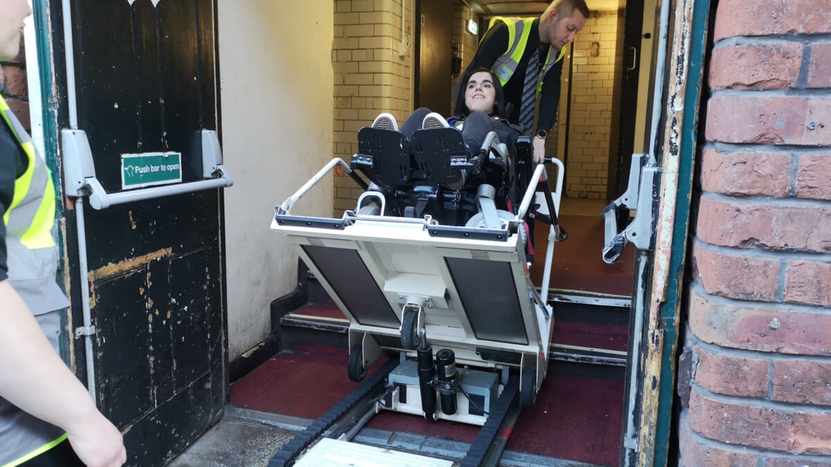 Emma is in her wheelchair and sitting in the stairclimber machine. It is tilted back. There is a steward standing behind the stairclimber and one standing in front.