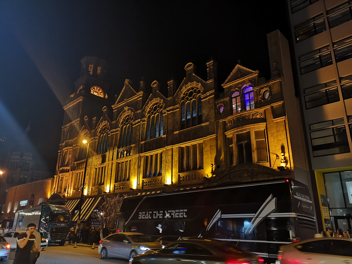 An exterior shot of the Albert Hall Manchester at night lit up. The bands tour bus is parked out front the venue.