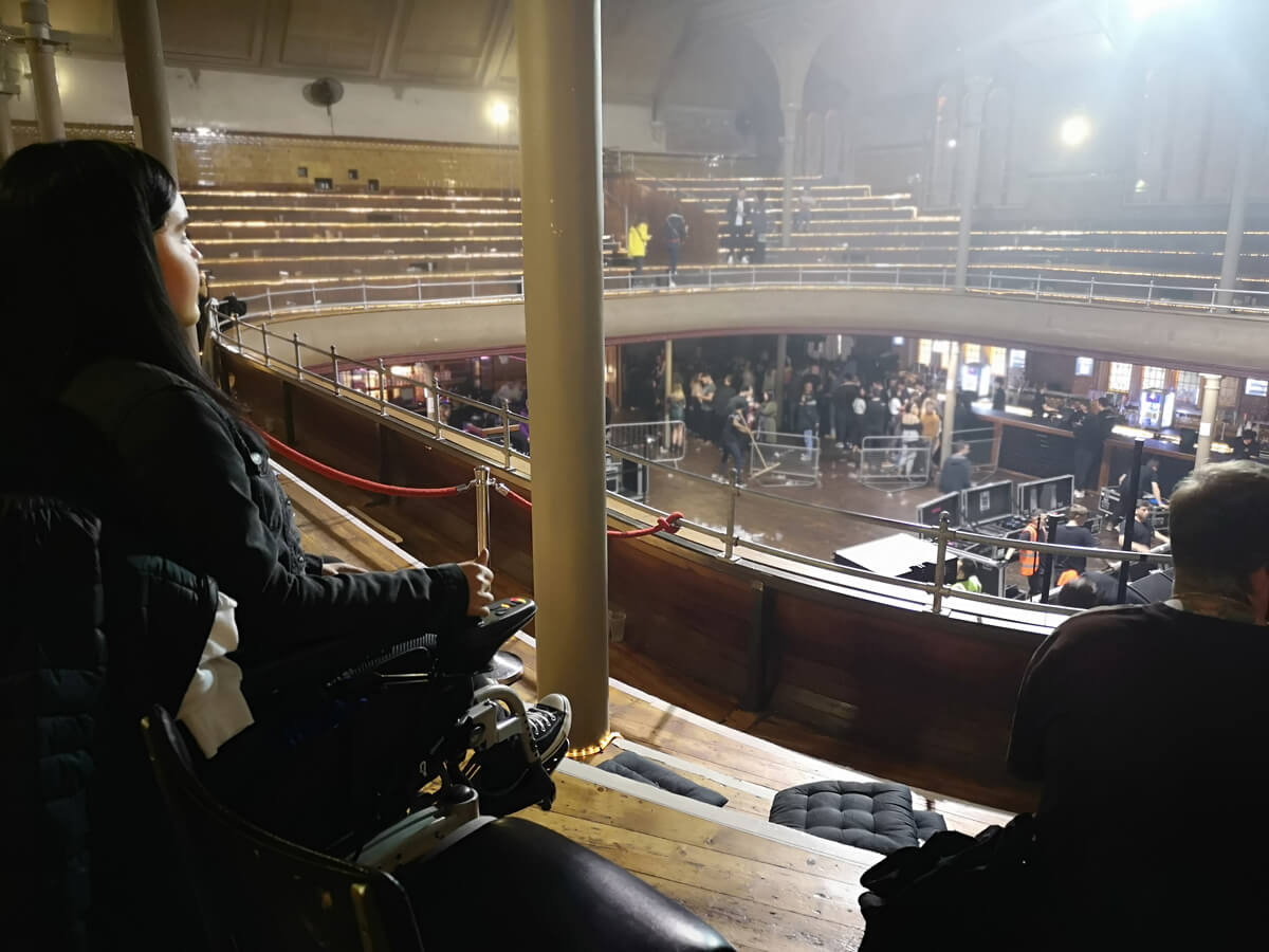 A side on view of Emma and her wheelchair sitting in the wheelchair accessible seating area at Albert Hall Manchester.