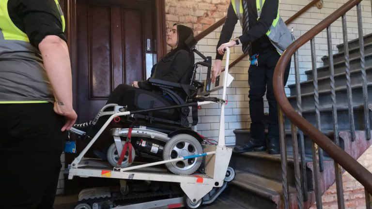 Emma is in her wheelchair and sitting in the stairclimber machine. It is at the bottom of the flight of stairs. There is a steward standing behind the stairclimber and one standing in front.