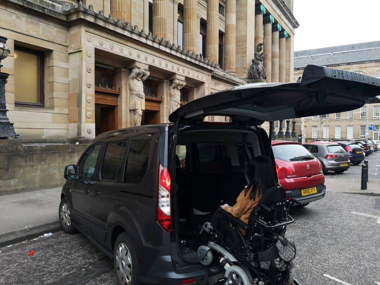 Emma driving her wheelchair down the ramp of her wheelchair accessible vehicle outside the Mitchell Library.