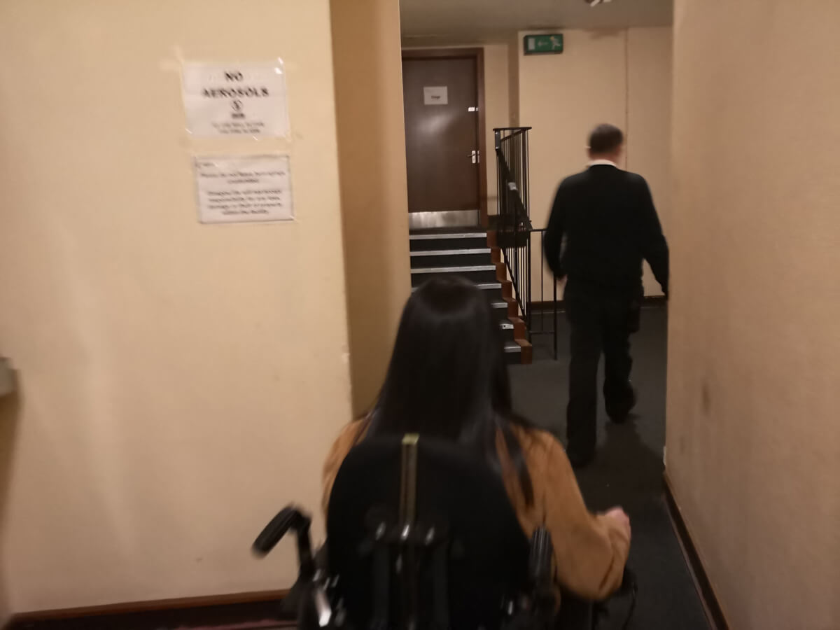 Emma being shown into the theatre through the accessible entrance.