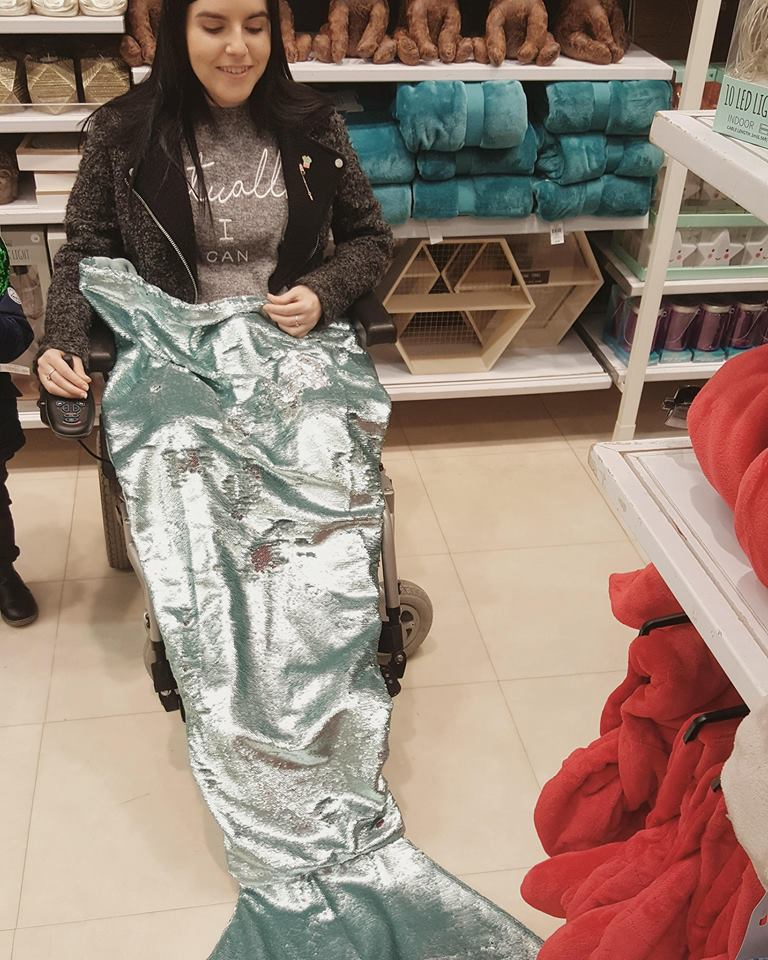 Emma is sitting in her wheelchair in a shop with a shimmery mermaid tail blanket over her legs.