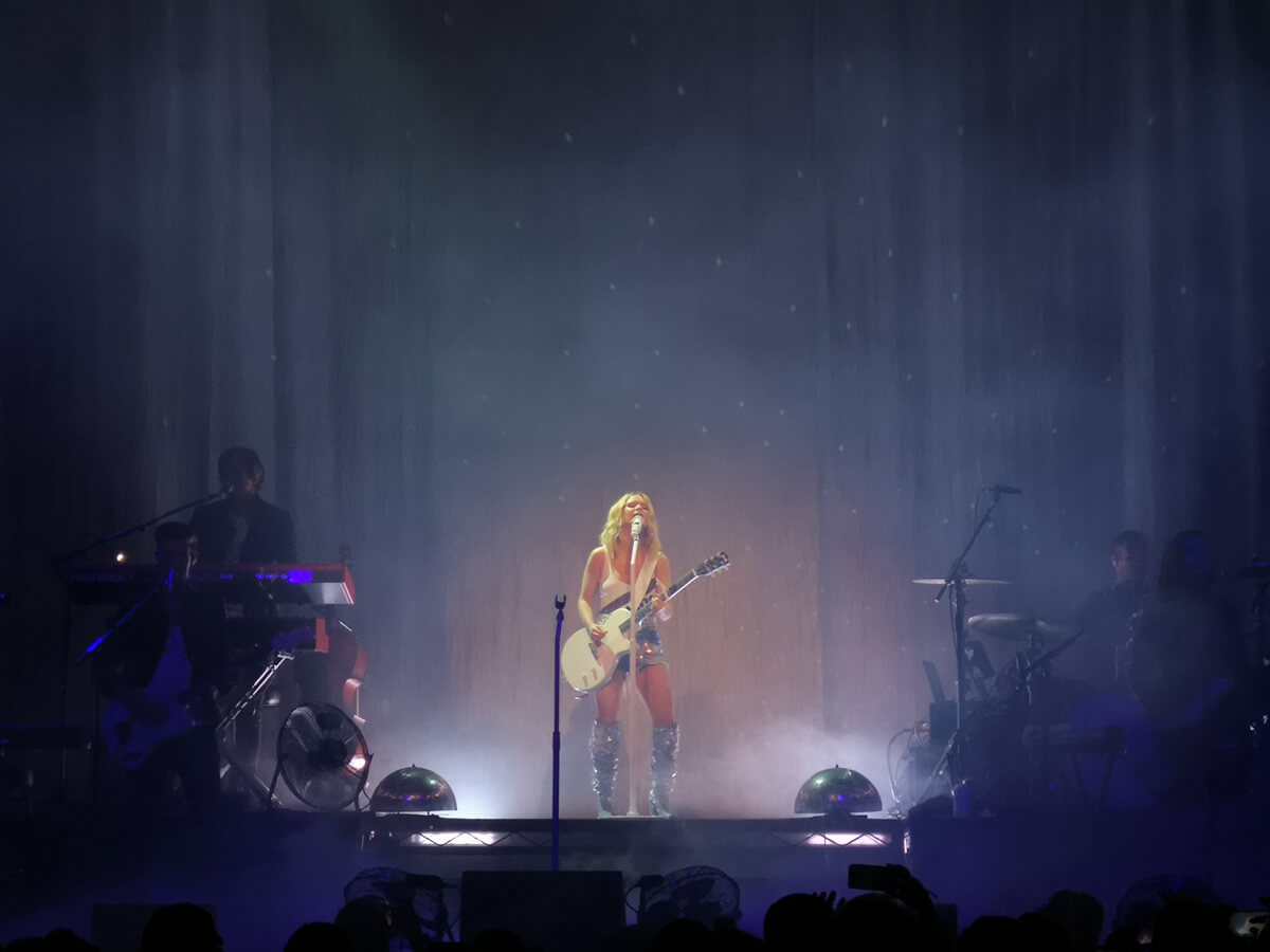 Maren Morris standing at the back of the stage opening the show. She is holding her guitar and wearing shorts and glittery knee-high boots.