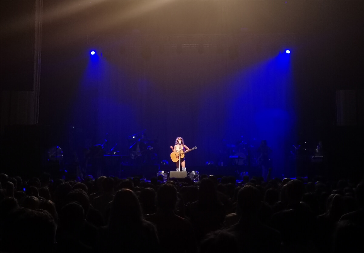 Maren Morris standing in the front and centre of stage on her own. She is standing holding her acoustic guitar.