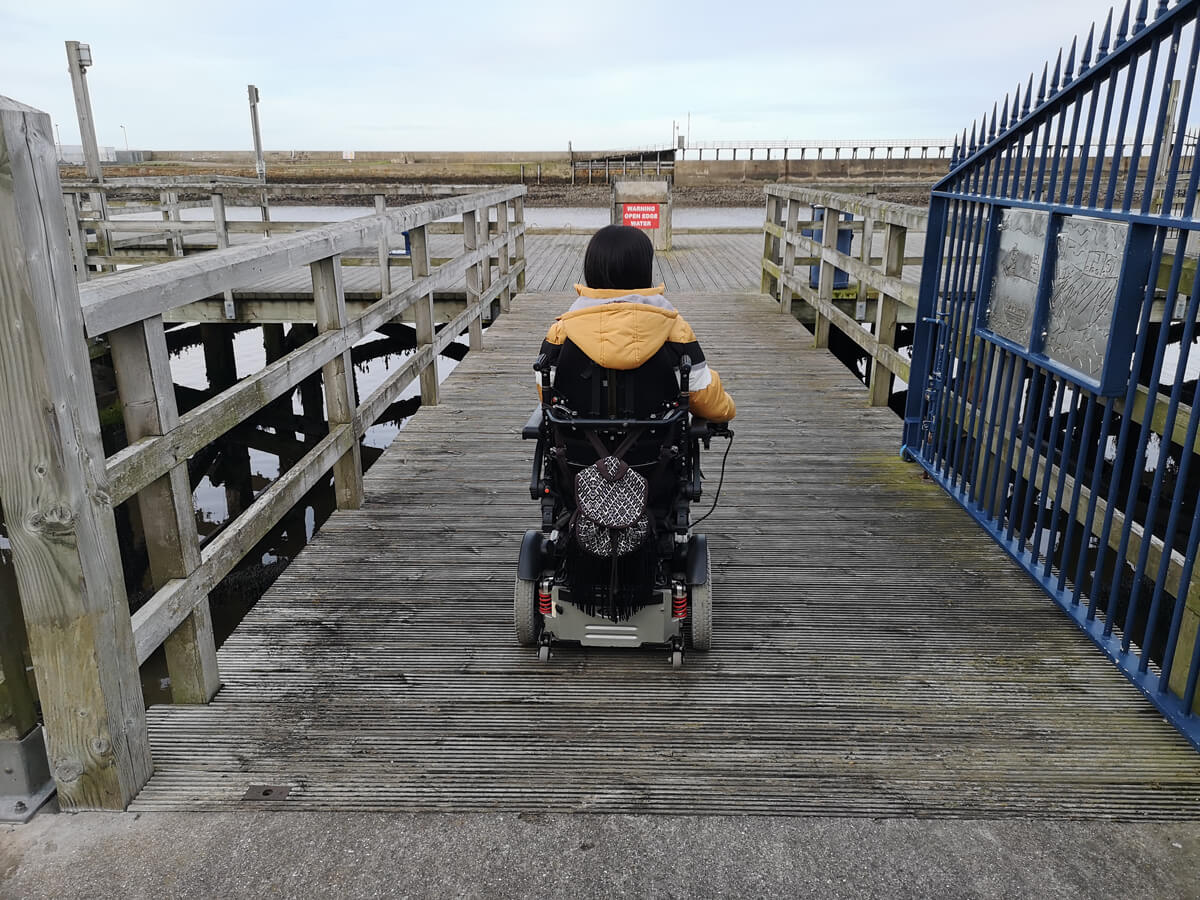 Emma driving her wheelchair on to the harbour in Blyth across from the hotel.