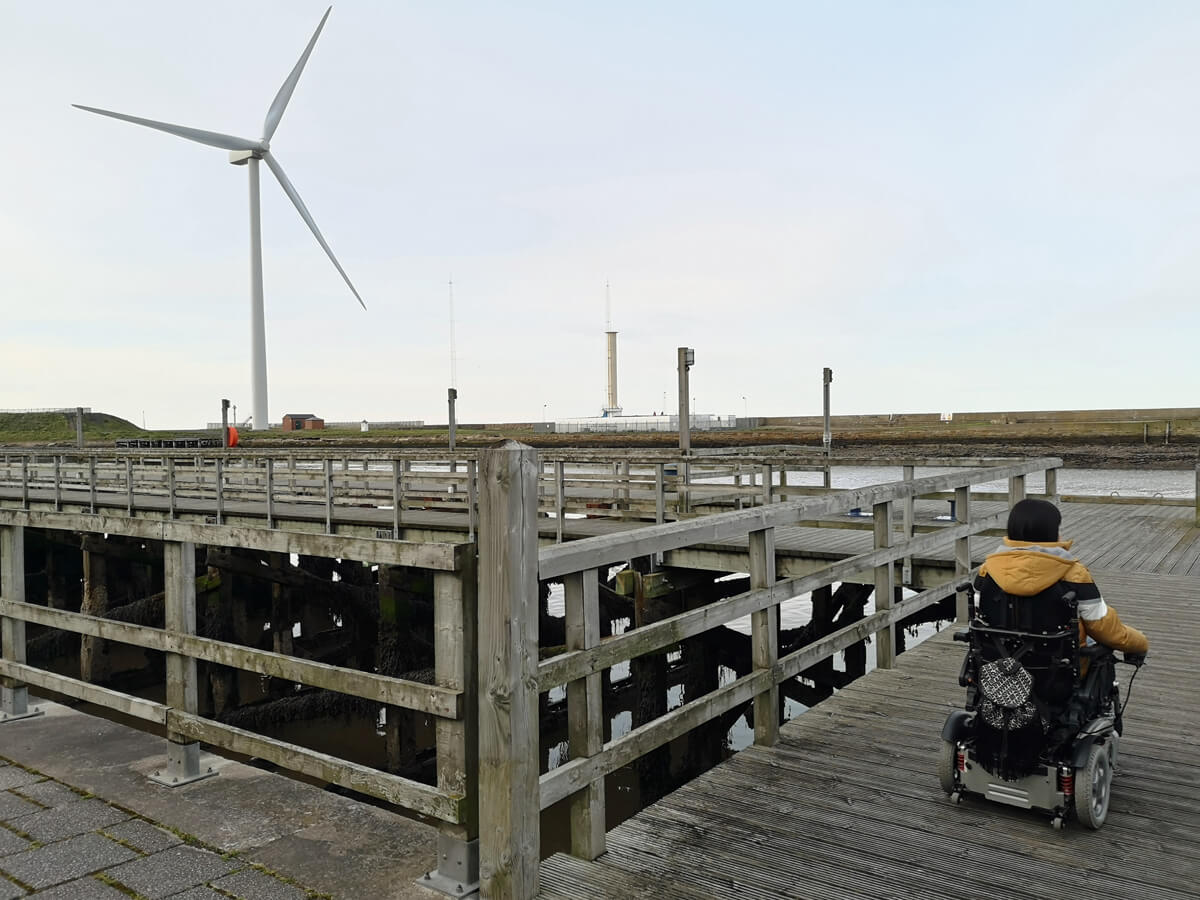 Emma driving her wheelchair on to the harbour in Blyth. Wind turbines are in the background.