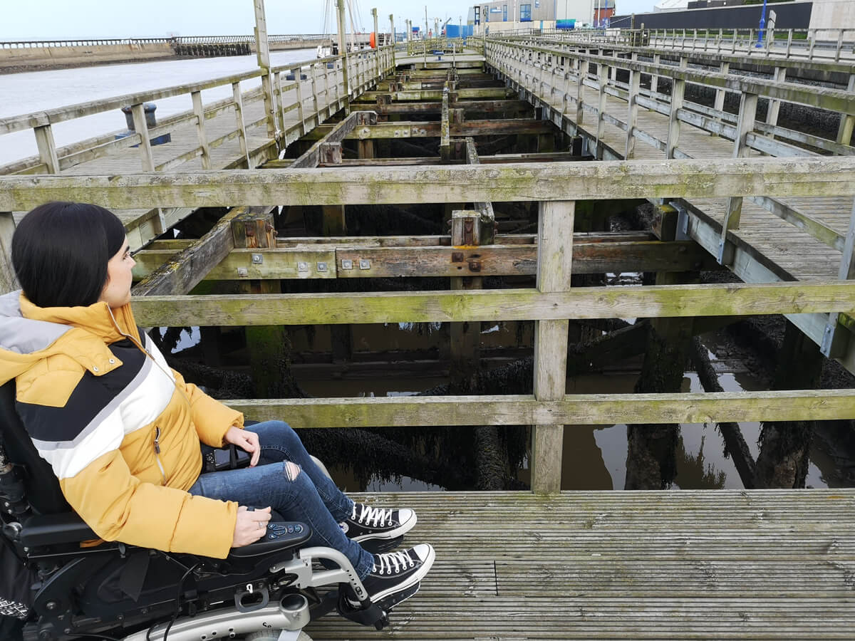 Emma sitting on the harbour. She is looking down at the water through the wooden beams.