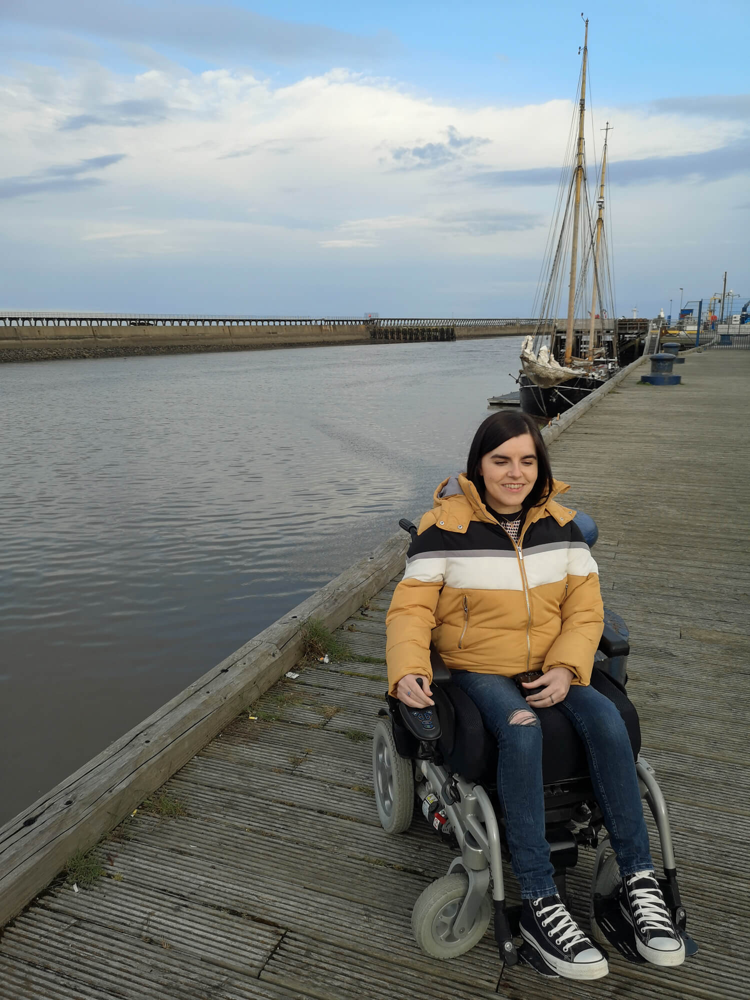 Emma is wearing a yellow, black and white puffy jacket, dark blue skinny jeans and black converse. She is on Blyth Harbour on a nice night. A boat is sitting behind Emma.