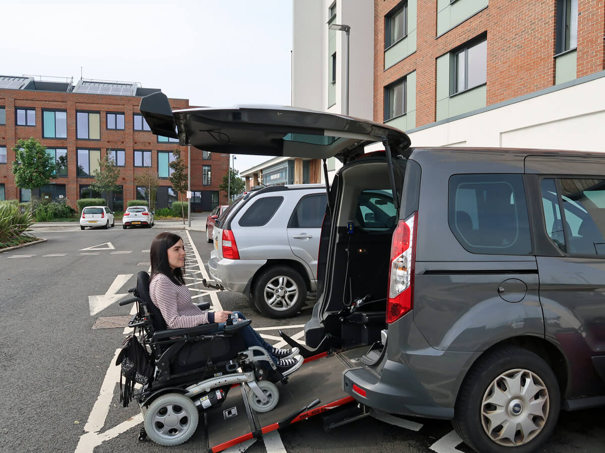 Emma in her powered wheelchair driving up the ramp of her wheelchair accessible vehicle at the hotel.