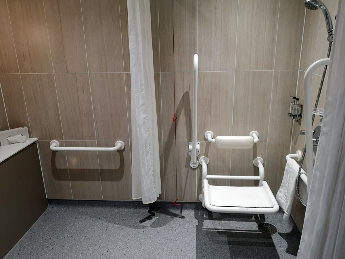 The roll-in shower and wall-mounted shower seat in our accessible room.