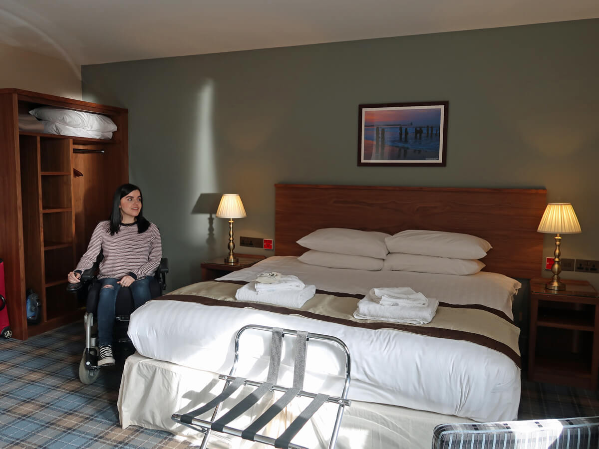 Emma is sitting next to the bed in the accessible room at The Commissioners Quay Inn.