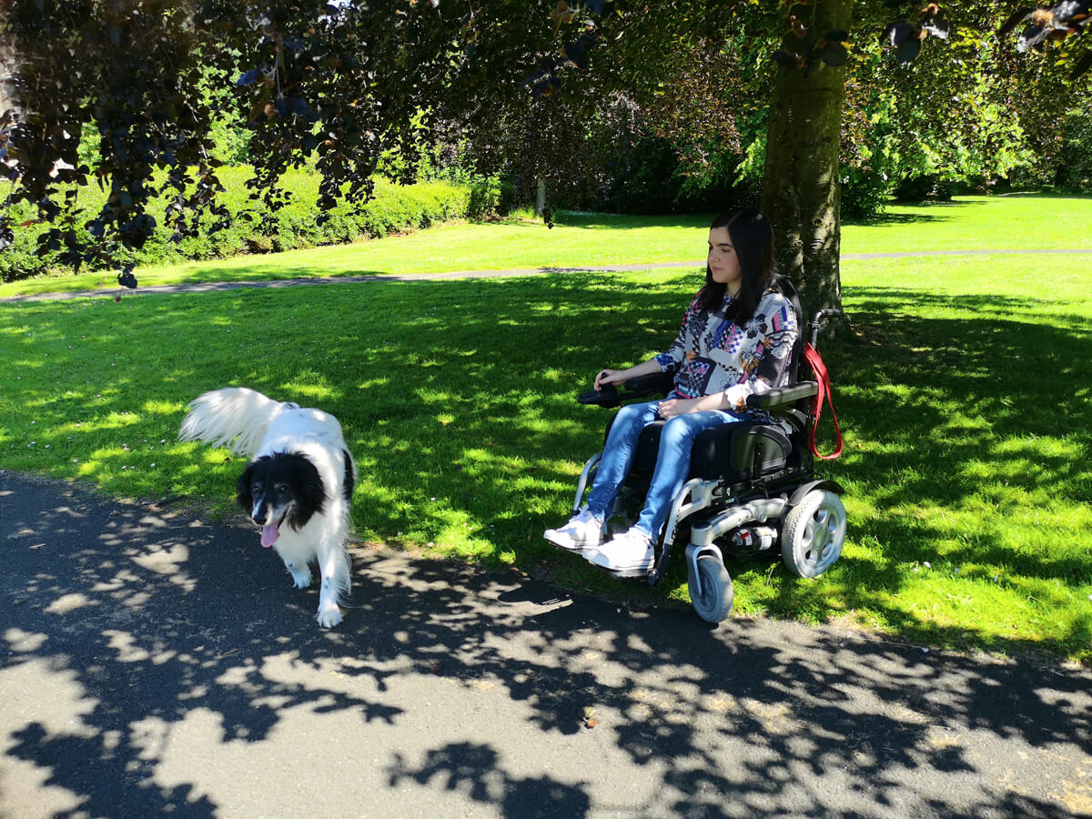 Emma is driving along a tarmacked path while Toby the dog is walking in front of her.