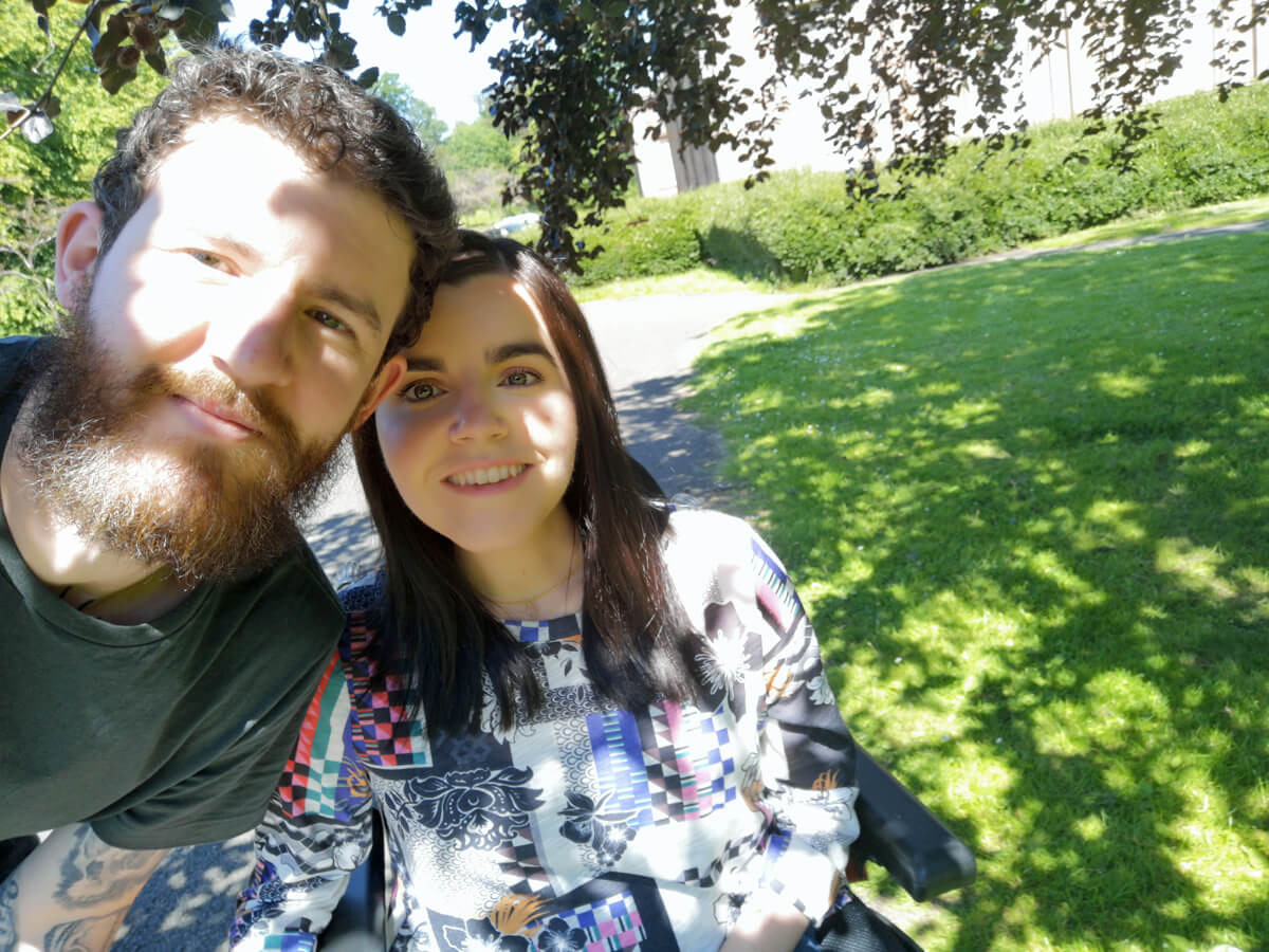 A selfie of Emma and Allan from the waist up. They are walking in the park on a sunny day.