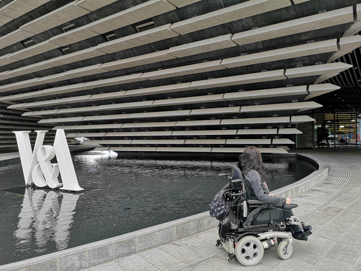 "Emma in her wheelchair with her back to the camera. She is facing the entrance of the V&A while sitting beside the swallow water surrounding the building. There are large white letters ""V&A"" sitting in the water."