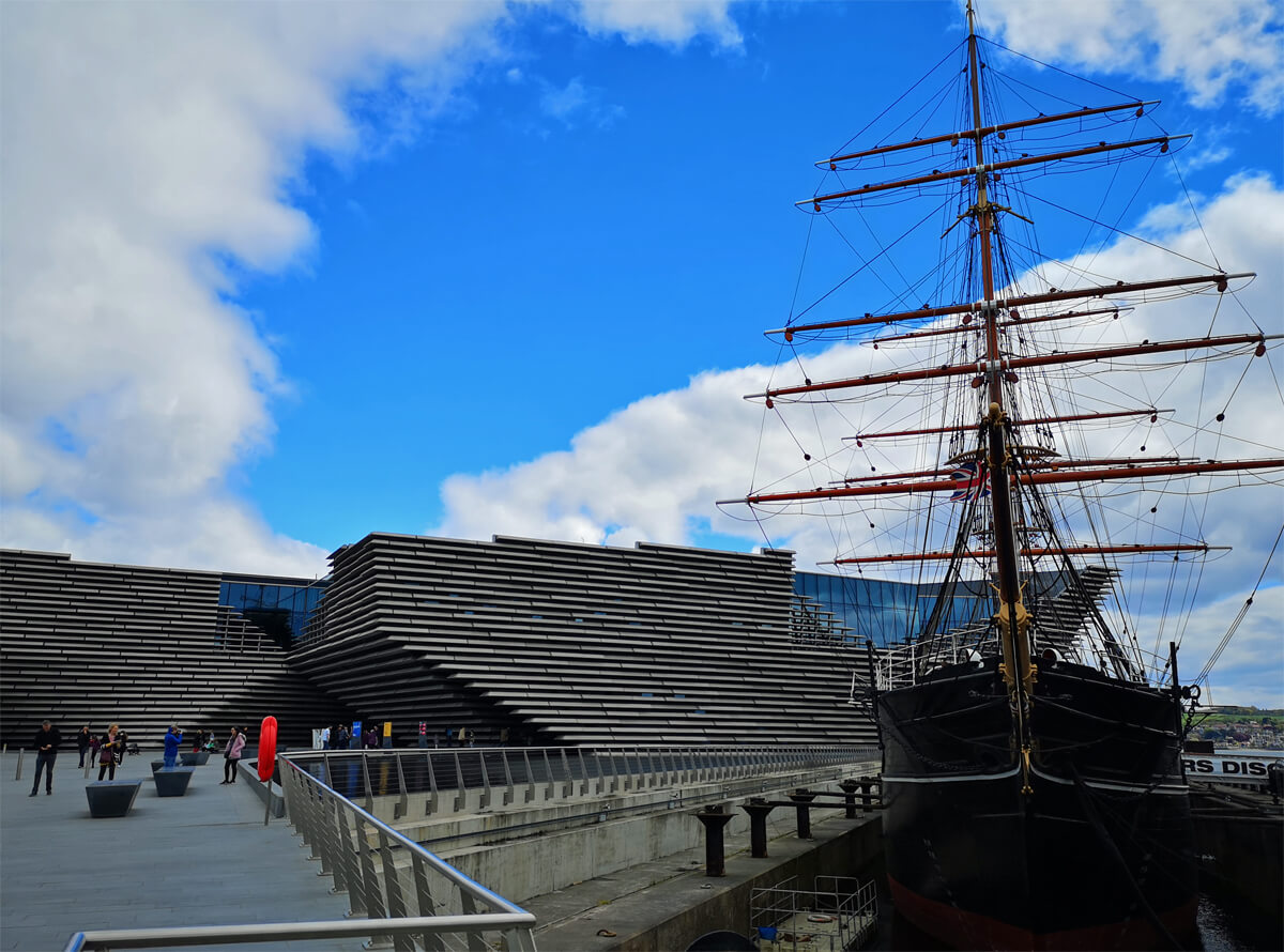 Exterior shot of the V&A Dundee against a blue sky with white fluffy clouds. The RRS Discovery ship is sitting beside V&A on the Dundee Waterfront.