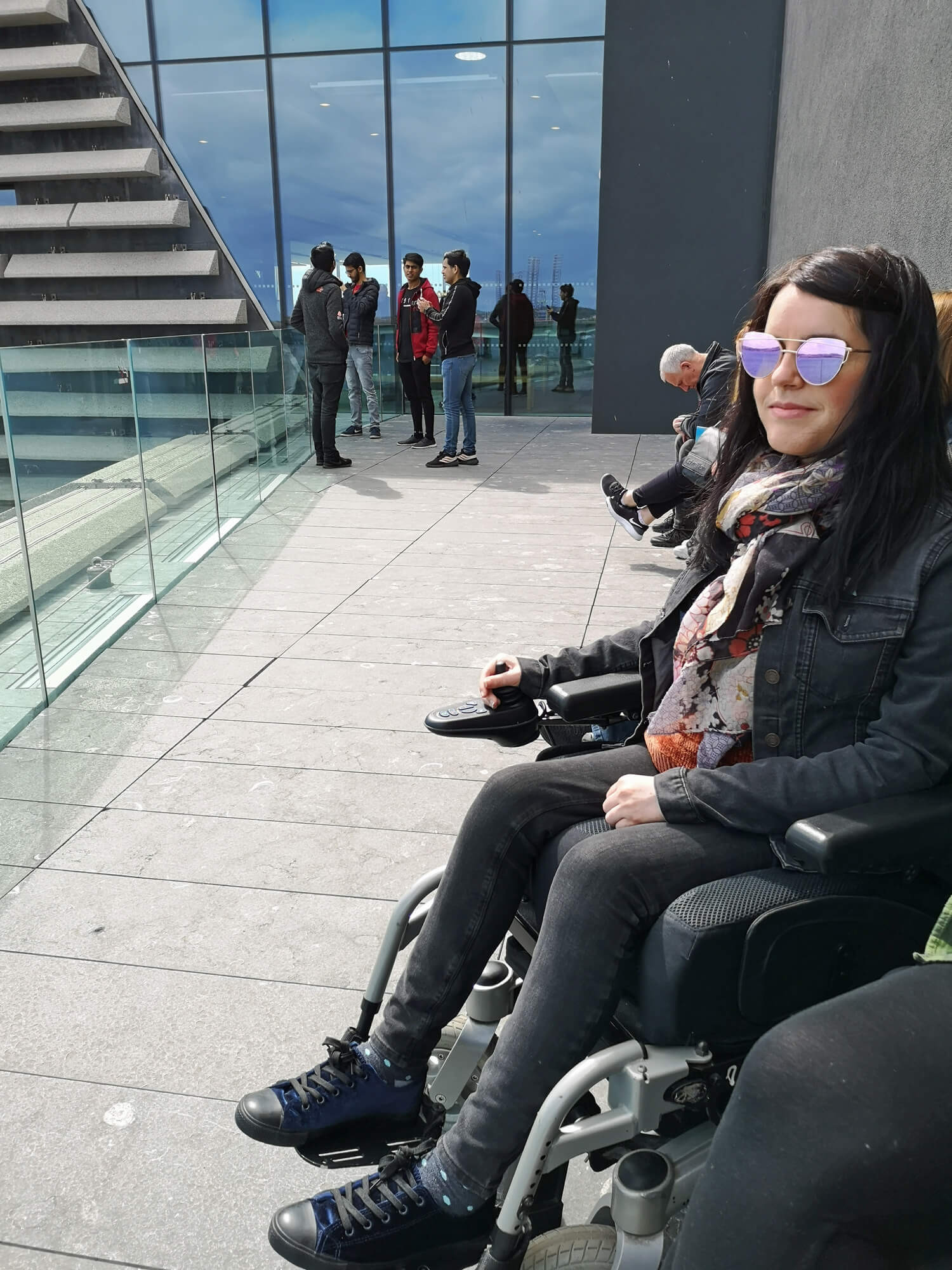 Emma sitting on the viewing terrace. She is wearing sunglasses, black denim jacket and black skinny jeans.