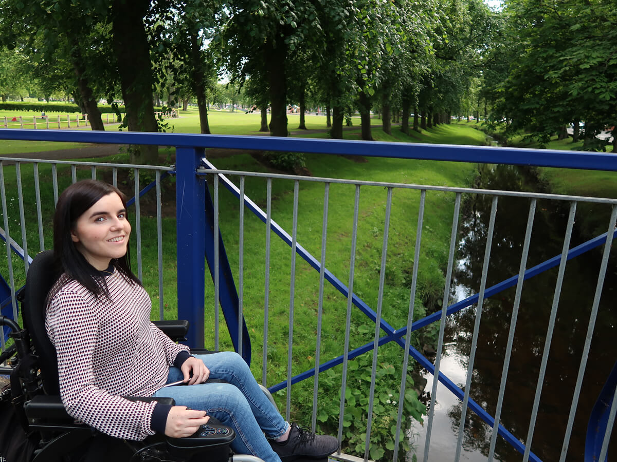 Emma smiling at the camera while sitting on a blue bridge with water streaming underneath.
