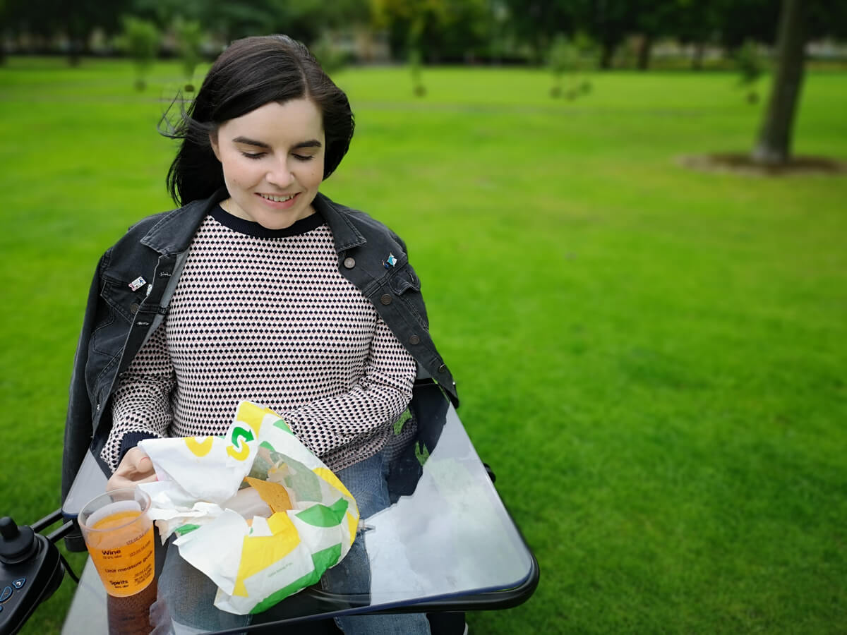 Emma having a picnic in the park. She is using her wheelchair tray table.