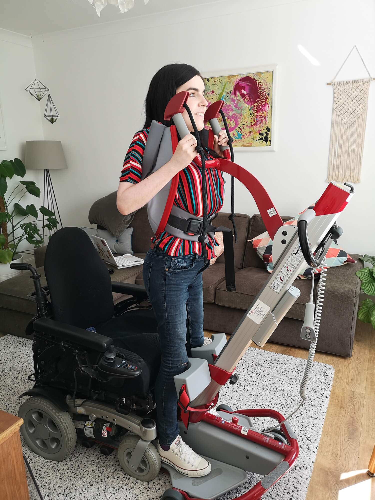 Emma standing up from her wheelchair using a Molift Quick Raiser sit-to-stand hoist. She is wearing a multicoloured striped shirt and is in her livingroom.