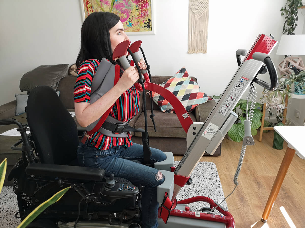 Emma being hoisted from her wheelchair using a Molift Quick Raiser sit-to-stand hoist. She is wearing a multicoloured striped shirt and is in her livingroom.