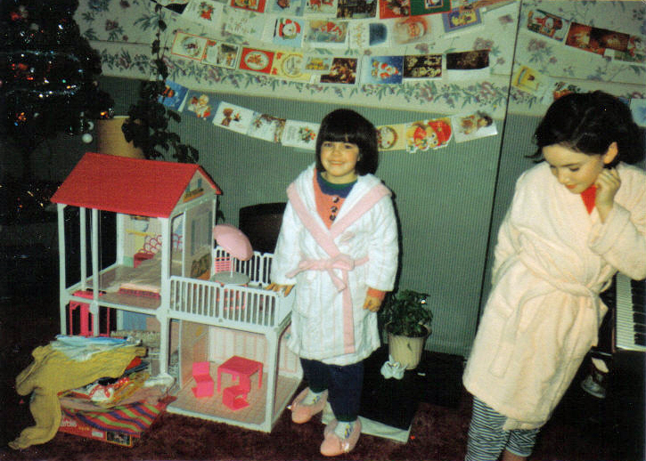Emma aged around 8 with her sister standing beside her. Taken on Christmas morning when Emma received a Barbie doll house.