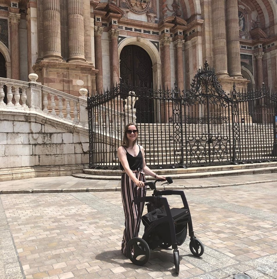Josephine Rees standing outside a grand building holding onto her wheelchair-and-rollator-in-1 mobility aid.