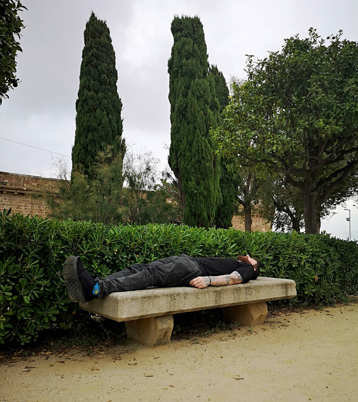 Allan lying on a concrete bench at Montjuïc Castle