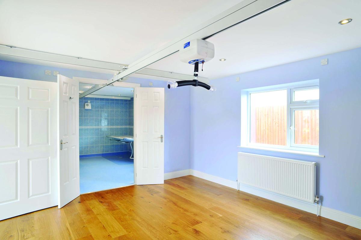 A stock photo of an empty bathroom with a ceiling track hoist leading into the bathroom.