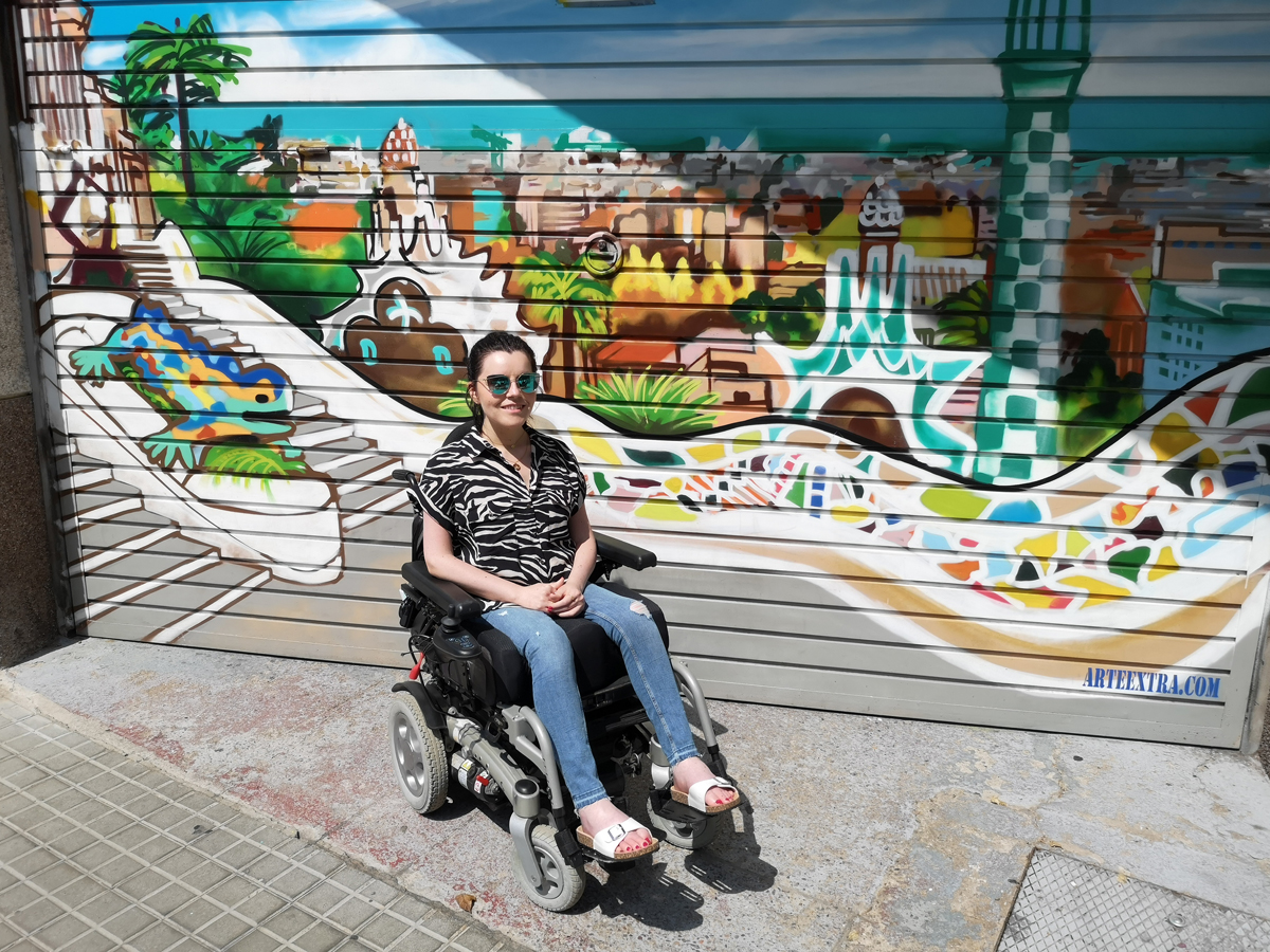 Emma sitting in front of a wall with Parc Güell street art