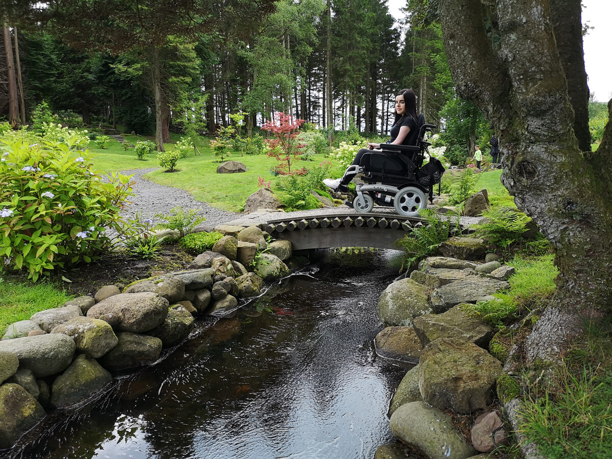 Emma crossing a small wooden bridge in her wheelchair with a stream flowing underneath.