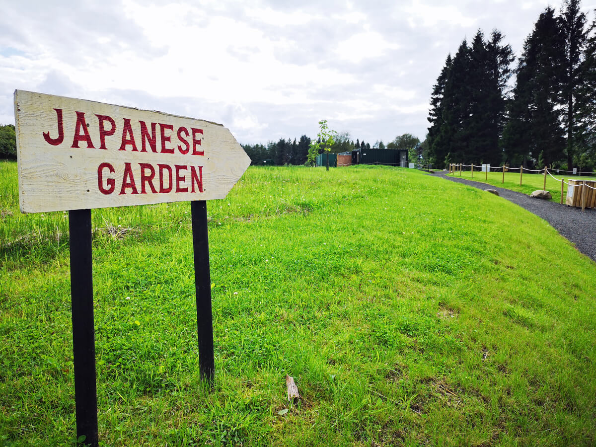 "A sign with ""Japanese Garden"" stuck in the grass showing the direction to the Japanese Garden."