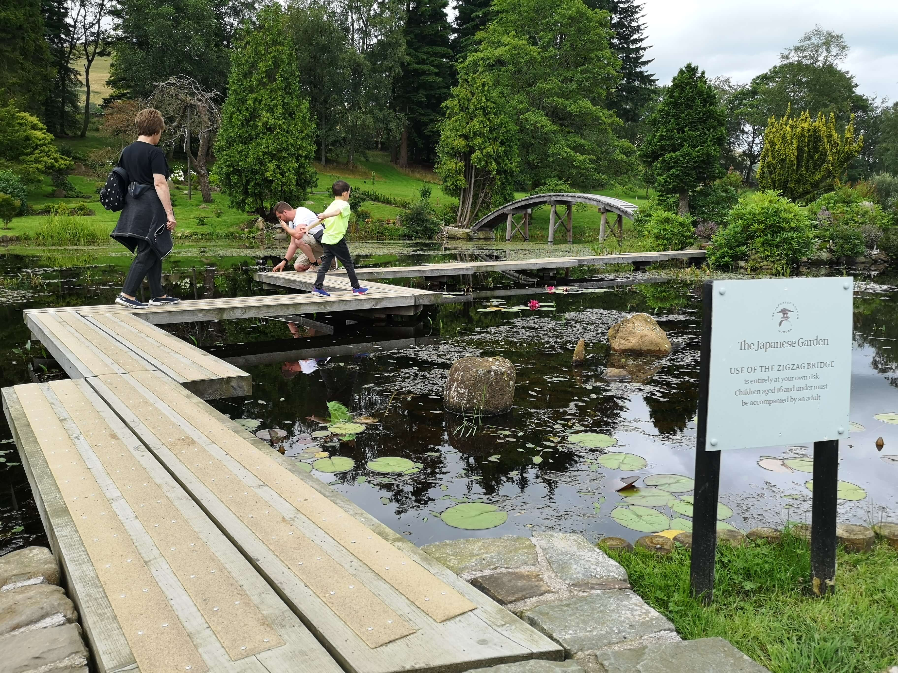 Emma's mum and nephew walking across a narrow path over the lily pad pond.