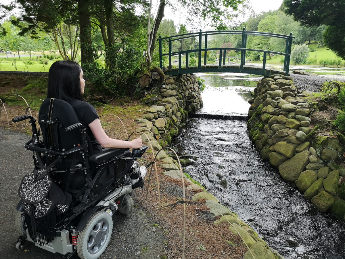 Emma sitting in her wheelchair facing towards the bridge that crosses the stream into the Japanese Garden.