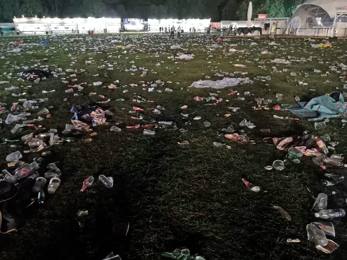 The ground covered with litter. The grass is covered with bottles, cups, food and ponchos.