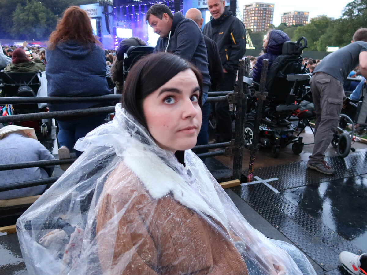 Emma is wearing a rain poncho. She is looking up at the camera with a worried look. She is disappointment by the lack of access on the viewing platform.