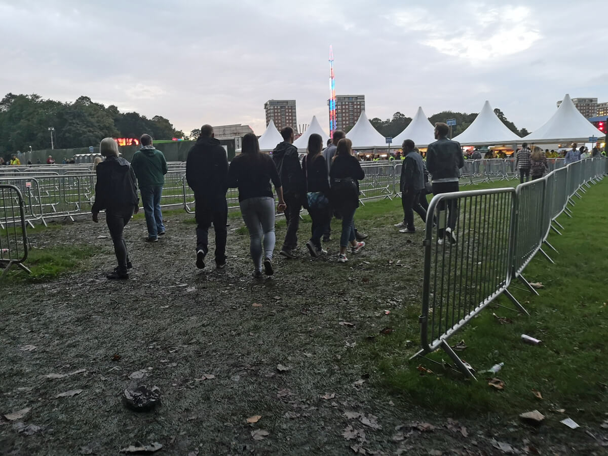 A muddy entrance at Fusion Festival. There are people walking across the muddy grass. There are no wheelchair mats on the grass.