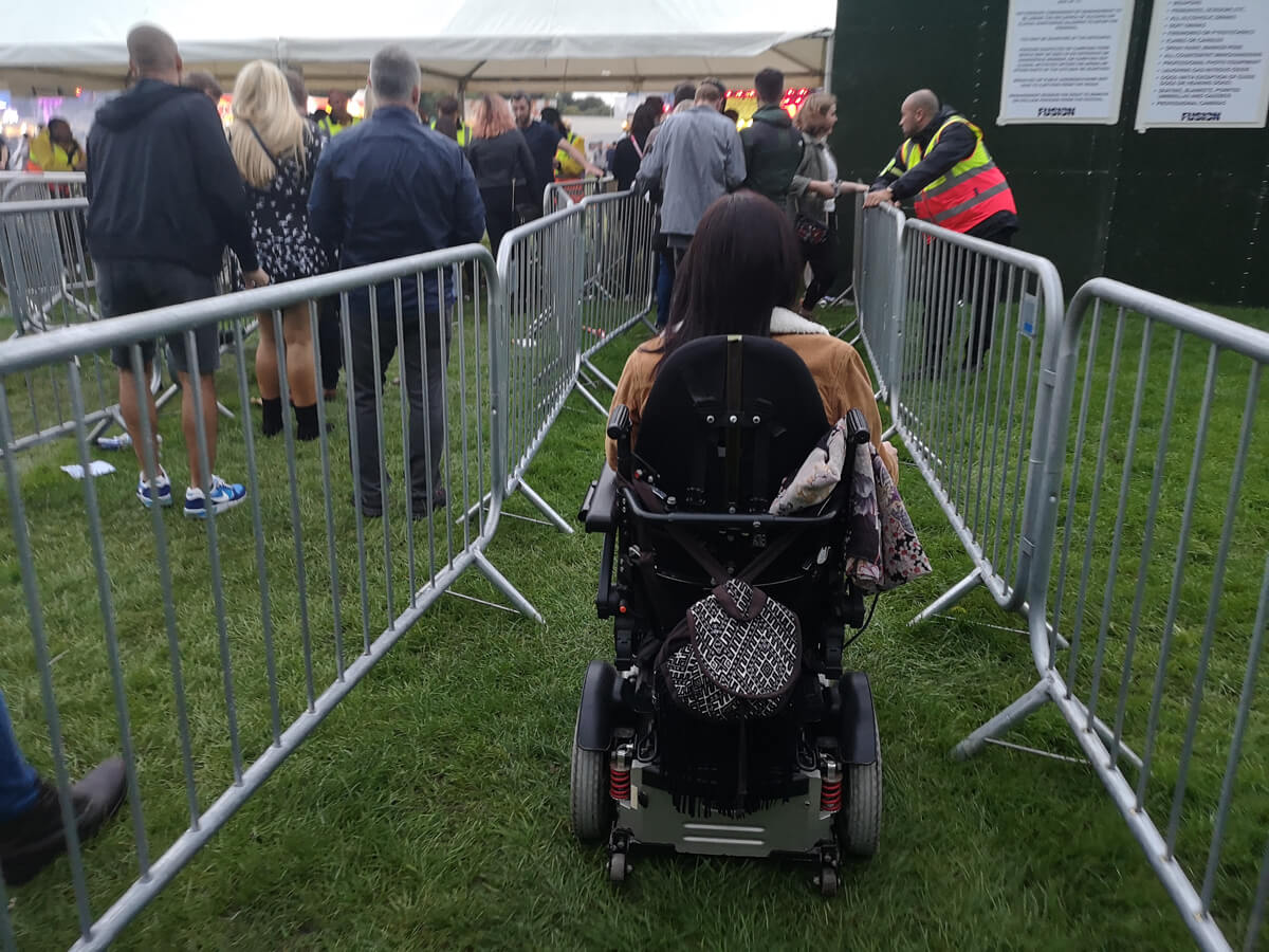 Emma in her powered wheelchair driving down the barrier lane into the festival.