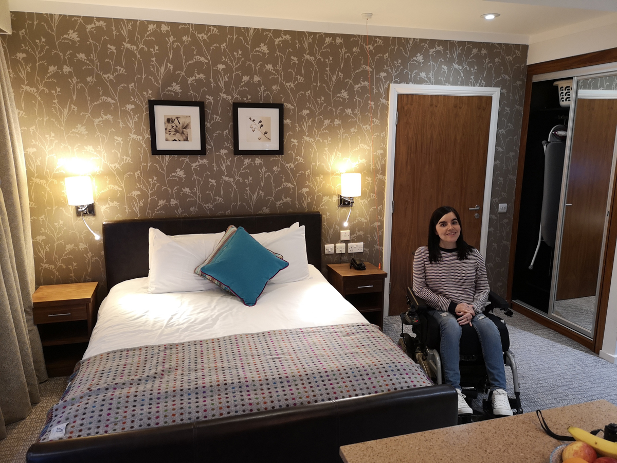 Emma sitting in her wheelchair next to the bed in her wheelchair accessible suite.