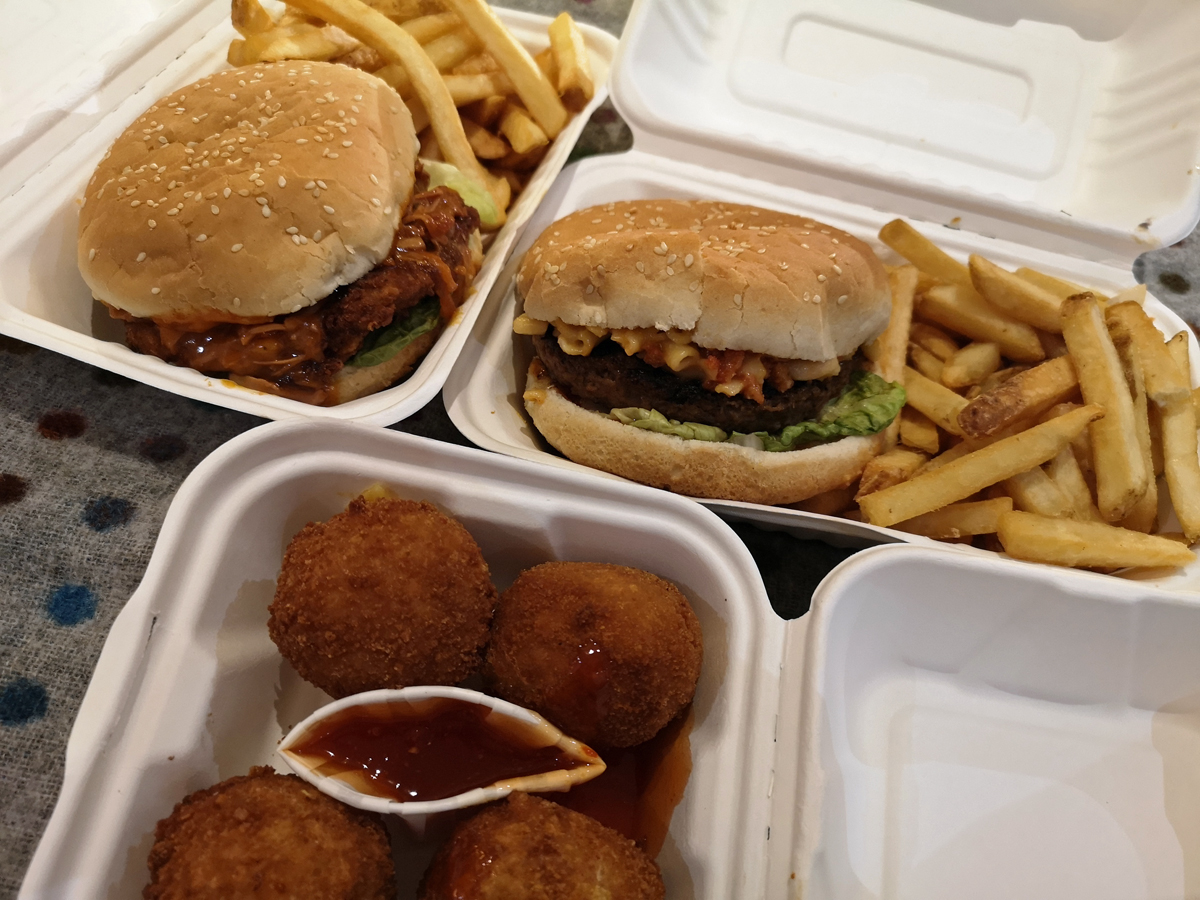 A close up of the food we ordered from Cali Vegan Kitch (The Caledonia Pub). Including two burgers, fries and mac bites.